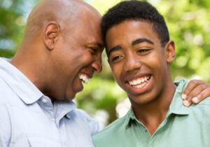 African American Father and Son Smiling and Embracing