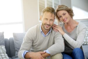 Couple Smiling Sitting In A Living Room